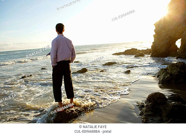Businessman at water's edge, El Matador beach, California, USA