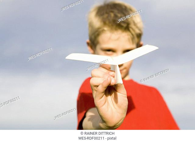 Boy 10-13 holding paper plane, close-up