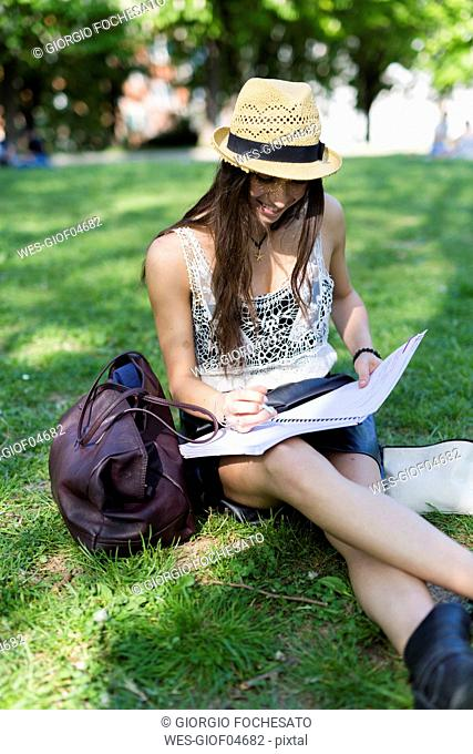 Smiling young student sitting on a meadow in a park using copybook