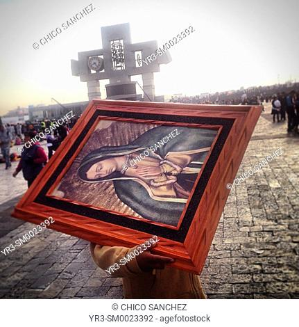 A man carries an image of the Virgin of Guadalupe during the annual pilgrimage to the Our Lady of Guadalupe basilica in Mexico City, Mexico