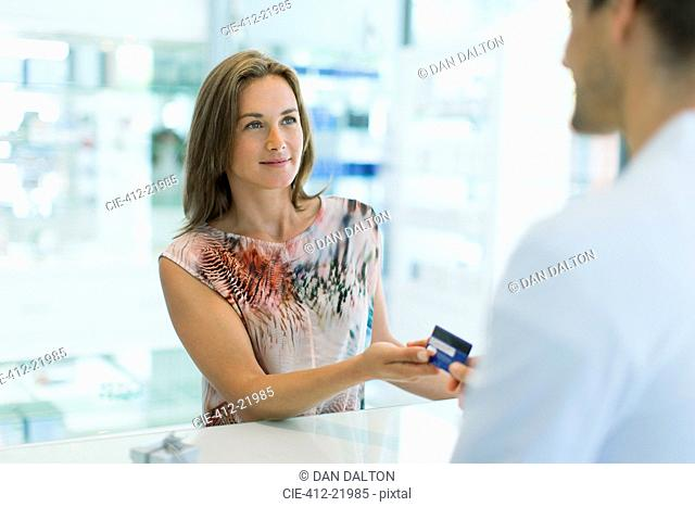 Woman paying with credit card in drugstore