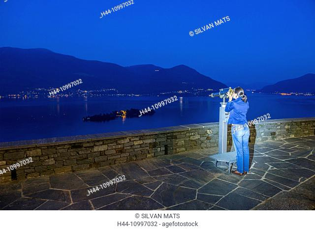 Woman using telescope in blue hour and watching Brissago islands on alpine lake Maggiore with mountain in Ticino, Switzerland
