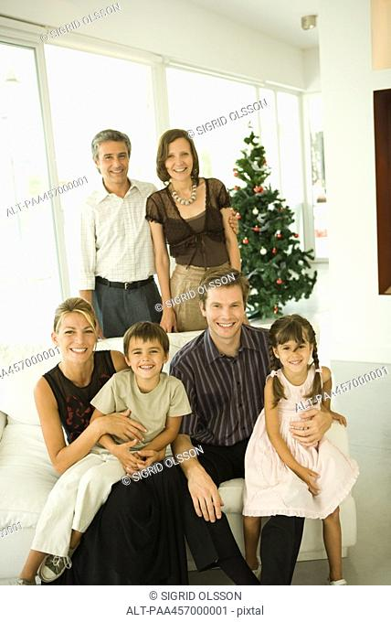 Three generation family, group portrait in front of Christmas tree