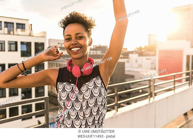 Portrait of happy young woman with headphones on rooftop