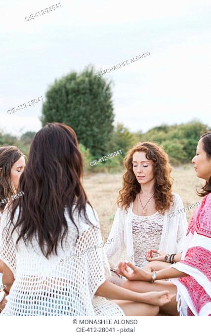 Boho women meditating in circle in rural field