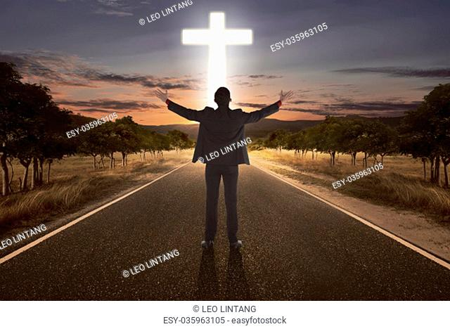 Portrait of man raising hand while praying to god with bright cross at the end of the road