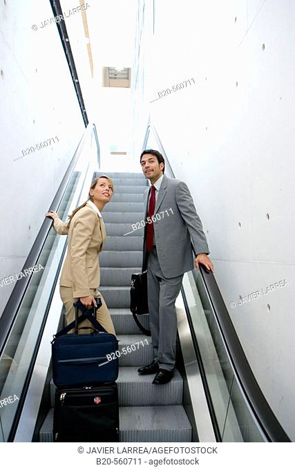 Businessmen travelling. Escalator