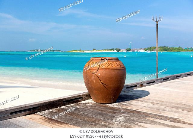 travel, tourism, vacation and summer holidays concept - maldives island beach with vase on wood flooring