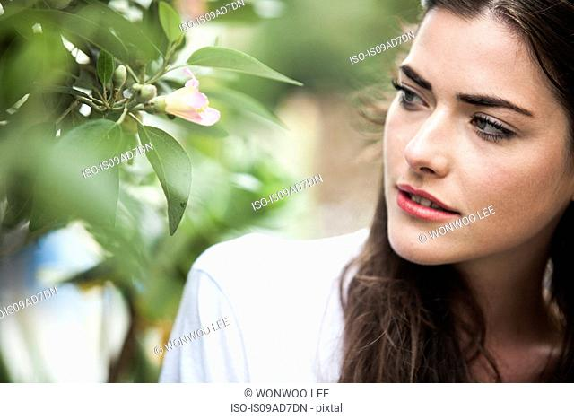 Close up portrait of young woman looking at blossom
