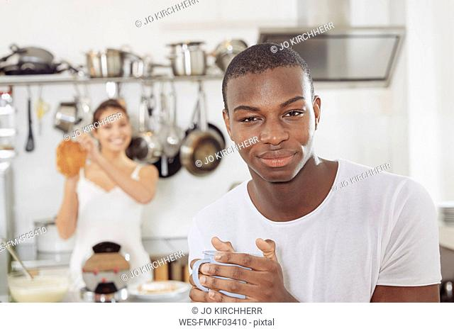 Portrait of smiling young man with coffee mug in kitchen