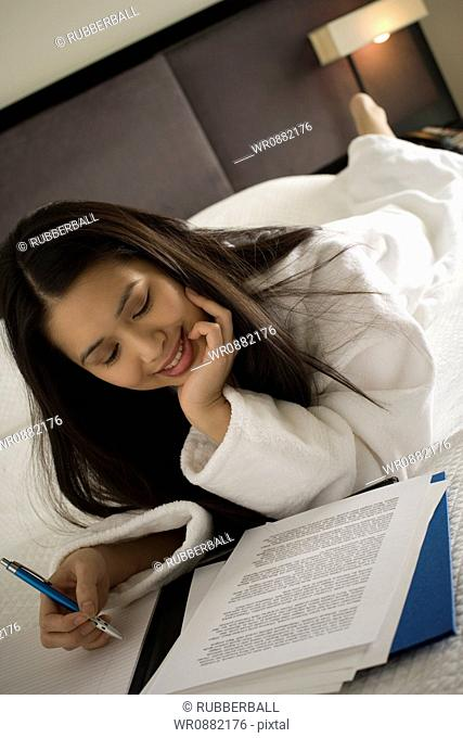 Close-up of a young woman reading sheets of paper holding a pen