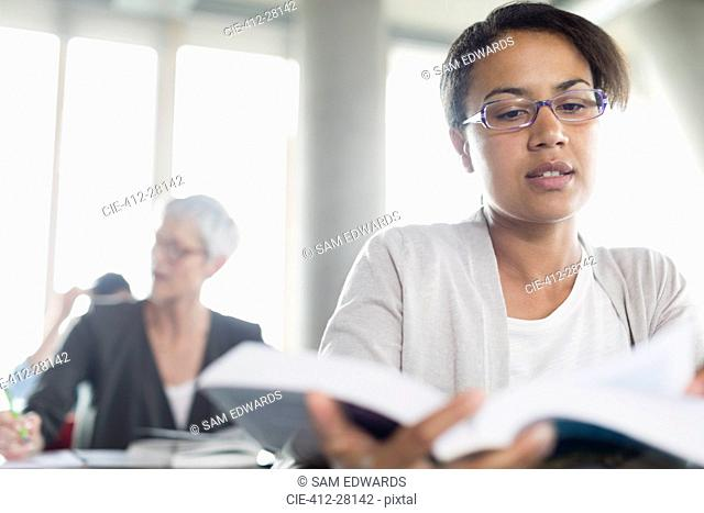 Serious woman reading book in adult education classroom