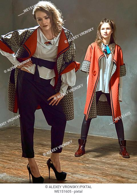 Photographing fashion collections of clothes in the Studio. Photos were taken opposite the dark gray walls. Two girls dressed in white blouses and dark red...
