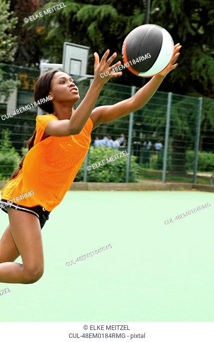 Woman playing basketball on court