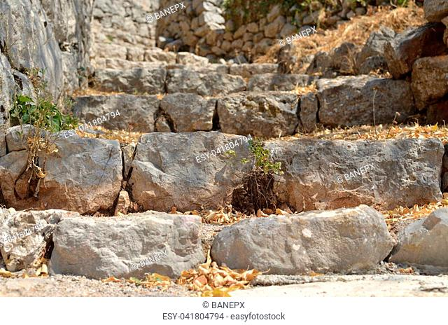 Rustic village stone stairs abandoned and overgrown with dry grass in summer