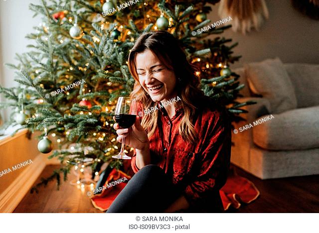 Woman laughing with wine beside decorated Christmas tree