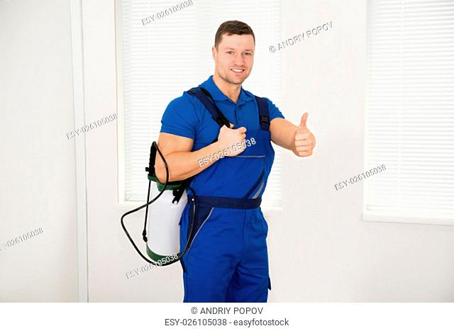 Portrait of confident male worker carrying pesticide container at home
