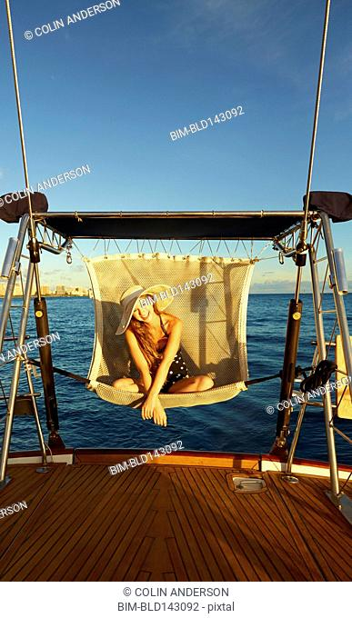 Caucasian woman relaxing in swing chair on yacht deck