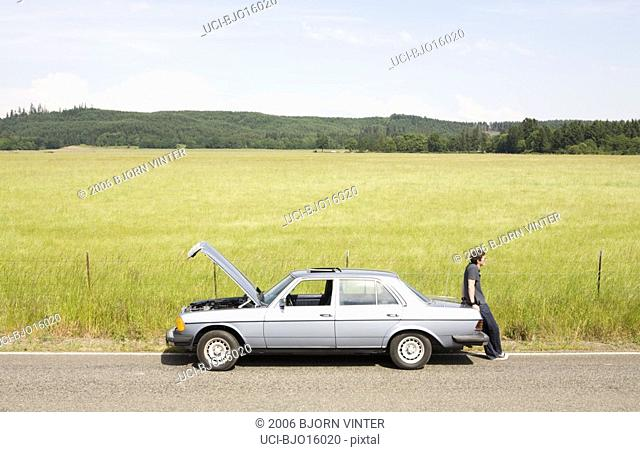 Man leaning on trunk of broken down car