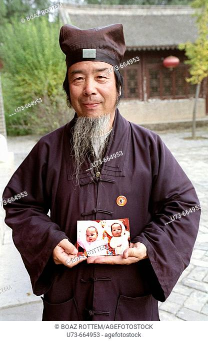 A Taoist monk hold a photograph of cute baby twins