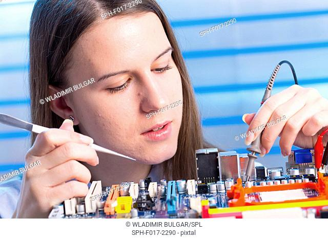 MODEL RELEASED. Young woman working on circuit board