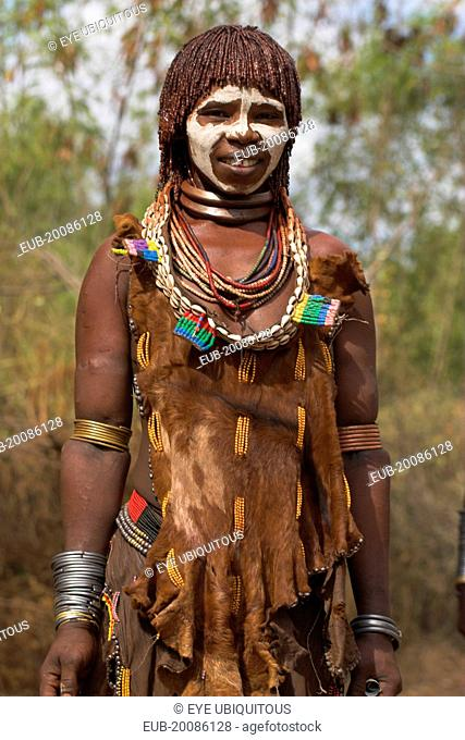 Woman with face painting, her hair greased with ocher colouring and animal fat into plaits known as Goscha and traditional goatskin dress decorated with cowrie...