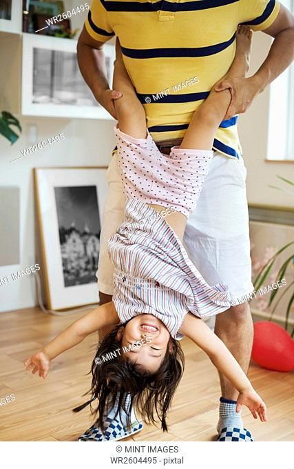 Family home. A man playing with his daughter, holding her upside down