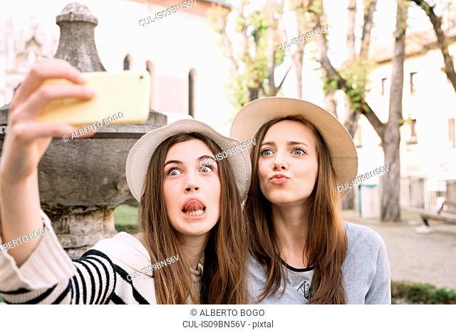 Girlfriends taking selfie at piazza, Belluno, Veneto, Italy