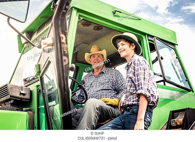 Portrait of farmer and teenage grandson with farm tractor
