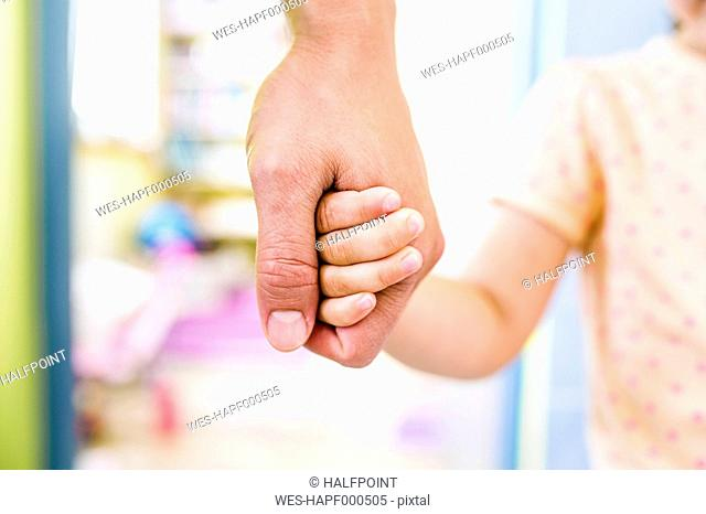 Father and daughter holding hands, close up