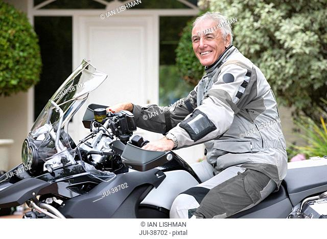 Portrait of smiling senior man on motorcycle in driveway