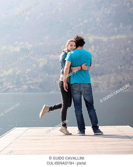 Young couple standing hugging on pier at Lake Mergozzo, Verbania, Piemonte, Italy