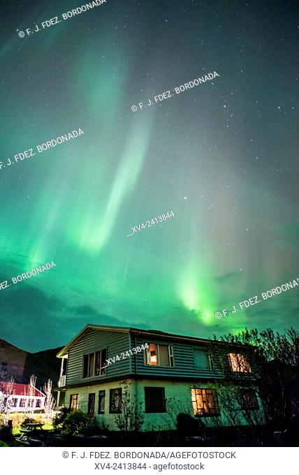 Northern lights above of houses of small village. Southern Iceland