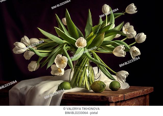 White flowers in vase with limes and blanket