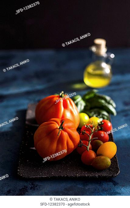 A bottle of olive oil behind a tray of various types of tomato