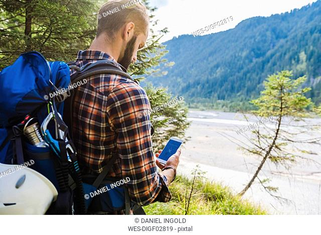 Hiker orientating with cell phone
