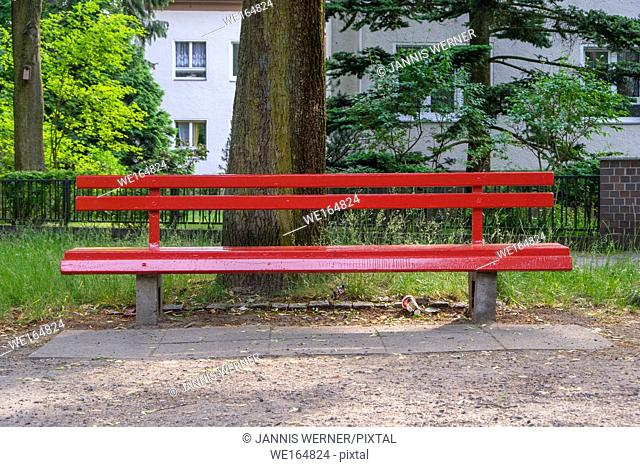 Red park pench at a street corner in Berlin-Zehlendorf, Germany
