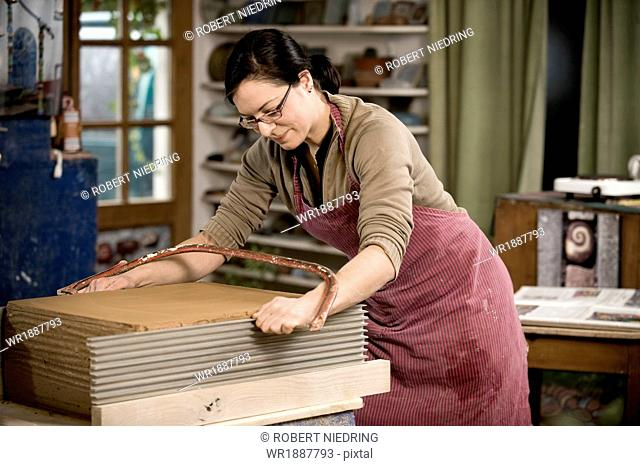 Craftswoman cutting clay in workshop, Bavaria, Germany, Europe