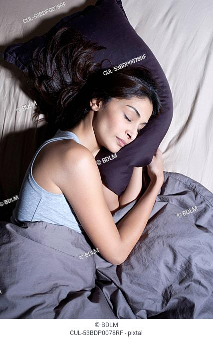 Sleeping woman cradling pillow in bed