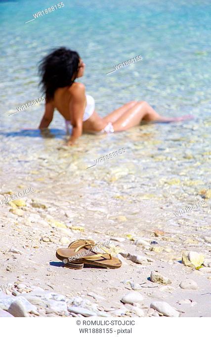 Young woman sitting in shallow water, Dugi Otok, Dalmatia, Croatia