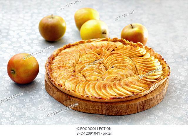 An apple tart on a wooden plate
