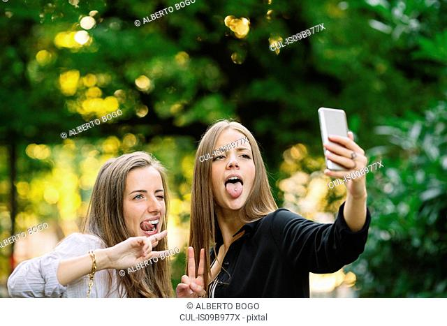 Two young female friends pulling faces for smartphone selfie in park