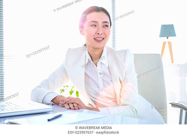 Smiling businesswoman with laptop and notes