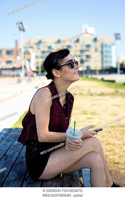 USA, New York City, Brooklyn, young woman sitting on a bench holding smartphone and plastic cup