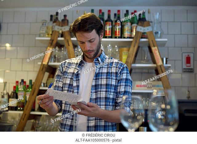 Shopkeeper reviewing paperwork