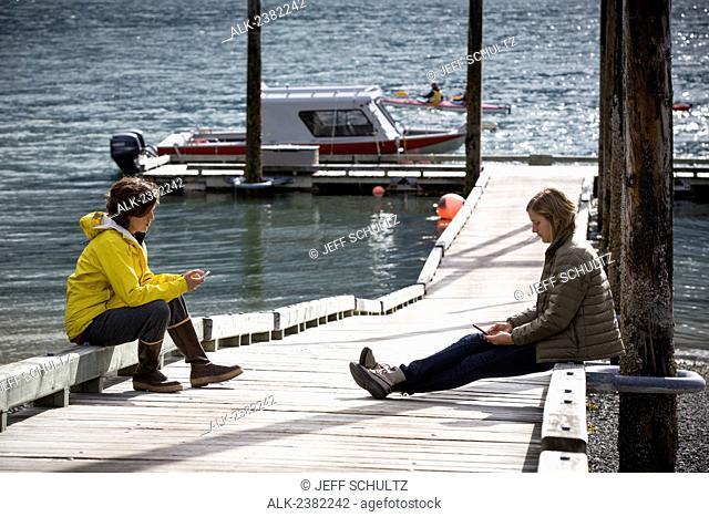 Women sitting on dock and using smart phone at Tutka Bay Lodge, Alaska, Summer