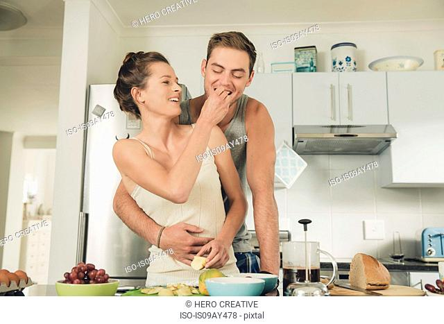 Romantic young woman feeding boyfriend whilst preparing breakfast at kitchen counter
