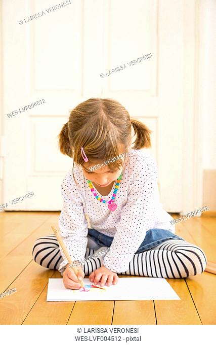 Little girl sitting on wooden floor painting with crayon