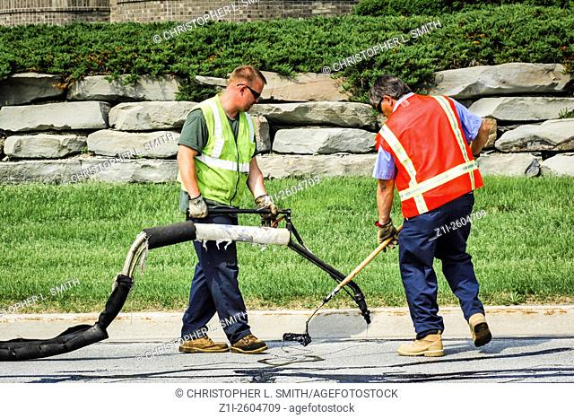 Road maintenance workers tarring in the cracked pavement
