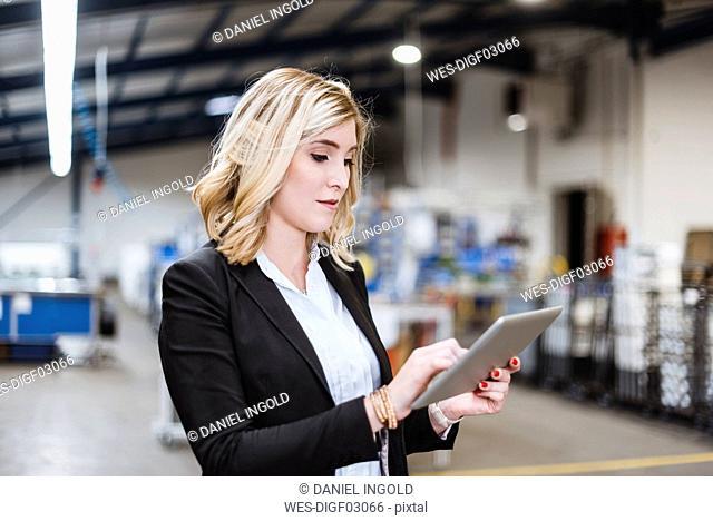 Blond businesswoman standing in shop floor, using digital tablet